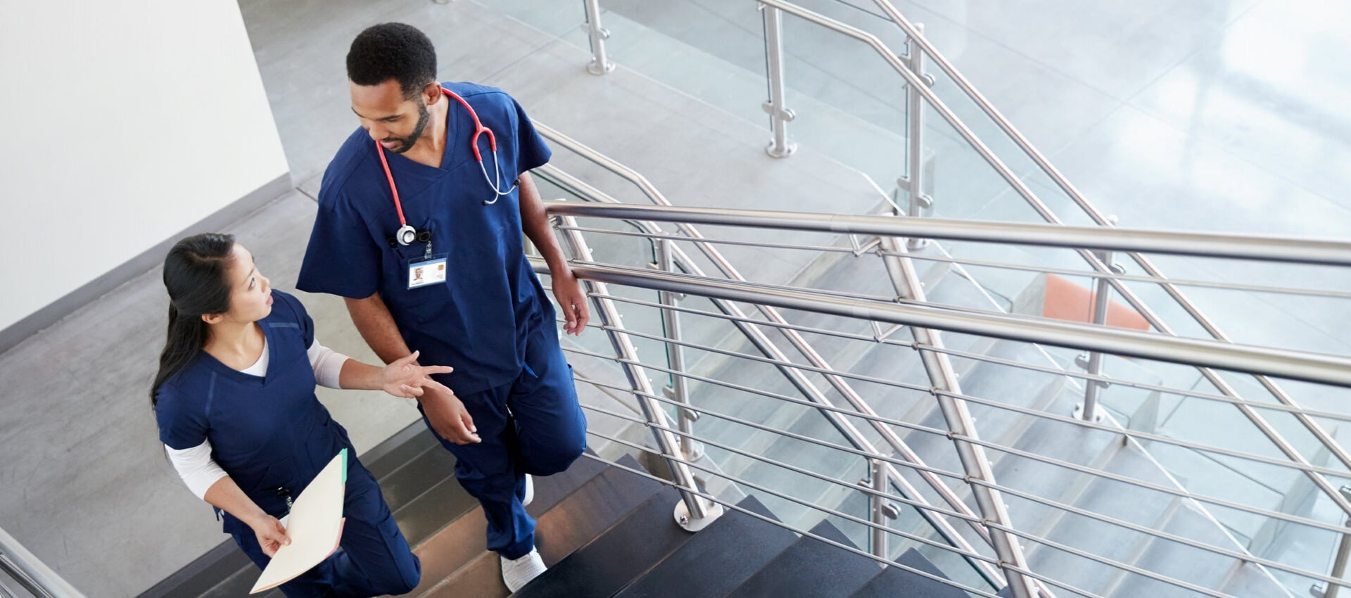 Nurses converse while ascending staircase.